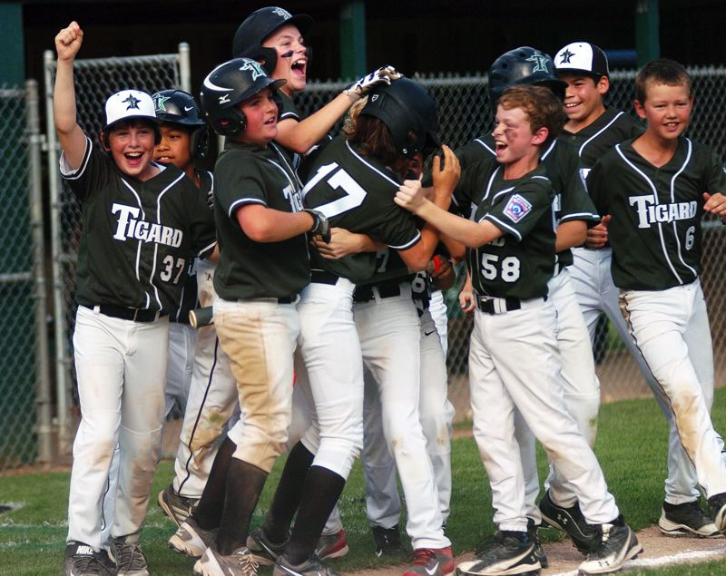 by: DAN BROOD - VICTORY -- The Tigard Little League 10-11 baseball team celebrates following the win over Cedar Mill.