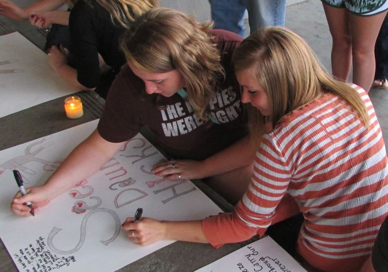 by: COURTNEY VAUGHN - Kylea Maughan and Stephanie Kundzmann sign posters for Seeaira Hicks during a candlelight vigil at St. Helens High School Tuesday, July 8. Maughan and Kundzmann went to school with Hicks.