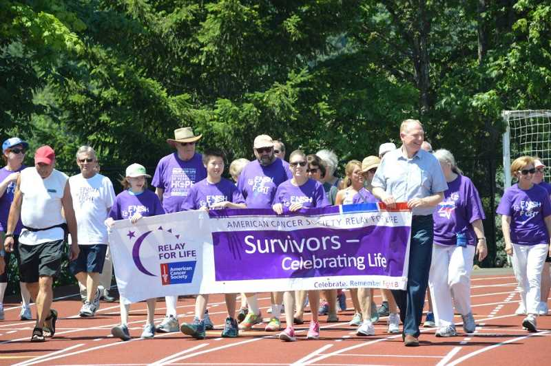 by: SUBMITTED PHOTO: RHONDA COHEN - A proud and happy moment at the 2014 Lake Oswego Relay for Life came when cancer survivors did a victory march around the high school track.