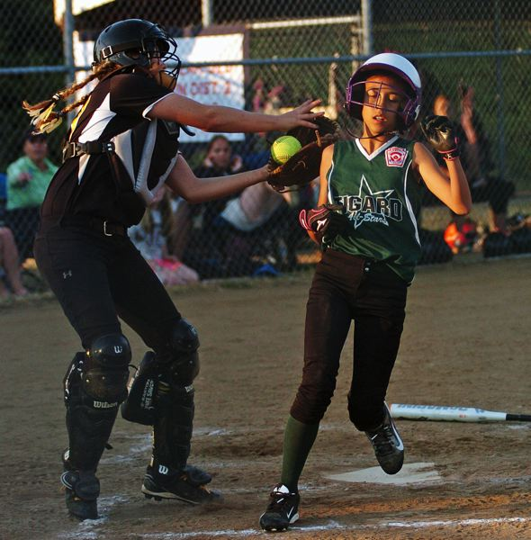 by: DAN BROOD - TIGARD RUN -- Tigard's Riley White (right)crosses home plate before Centennial catcher Savannah Darling can make a tag.