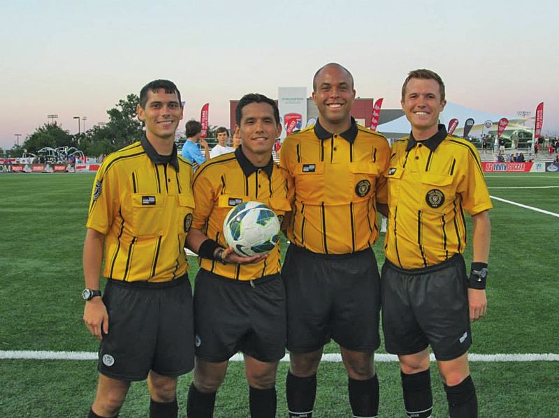 by: JOHN WILLIAM HOWARD - Scappoose graduate Andy Deuker (right) has been able to visit 18 different states and officiate matches from youth national championships to Pac-12 games, all the way to matches for the Portland Thorns.