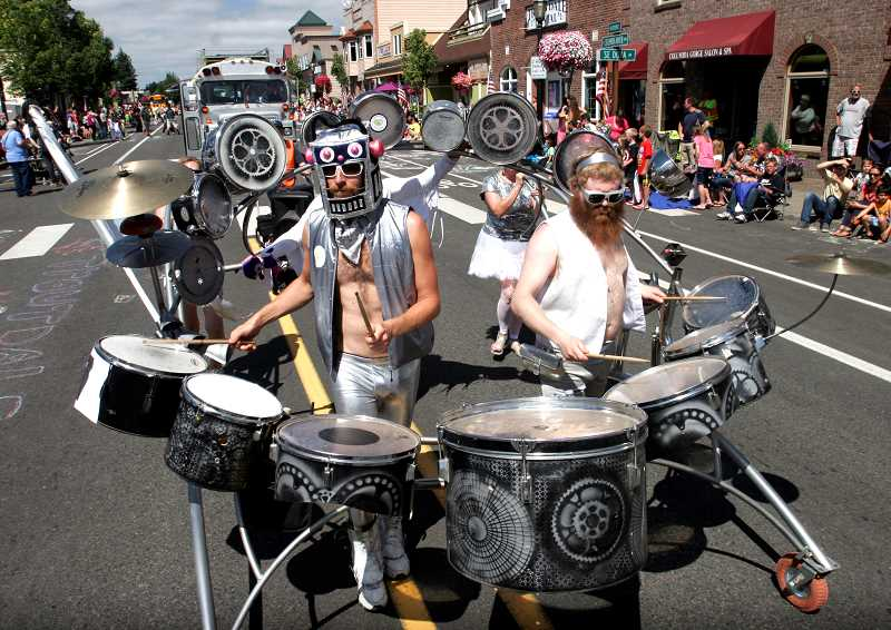 by: OUTLOOK PHOTO: JIM CLARK - Members of the Love Bomb Go Go band take part in the SummerFest  parade on Saturday.