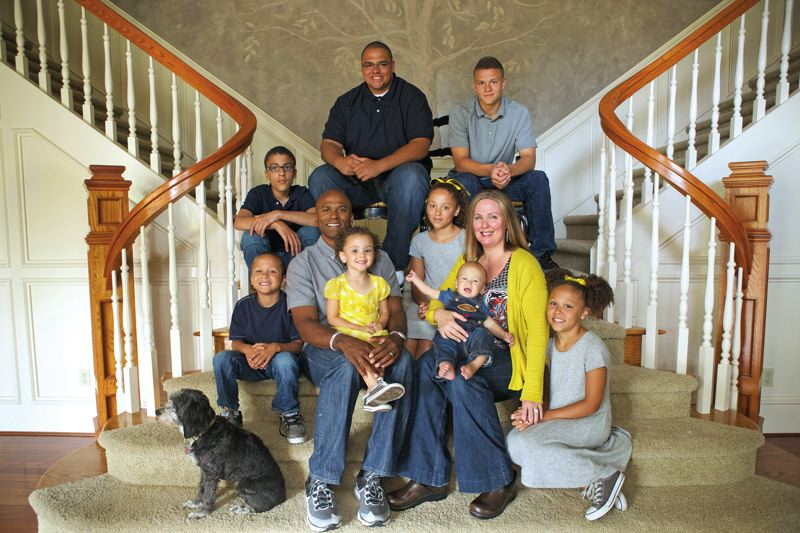 Photo Credit: TRIBUNE PHOTO: JAIME VALDEZ - The Molden family at home in West Linn: front row (from left) Josiah, 5; father Alex, a former University of Oregon star cornerback; Bianca, 3; Alana, 10; Ezra, 8 months; Alexs wife Christin; and Selah, 8. Back row: Micah, 12; Isaiah, 18; and Elijah, 15.