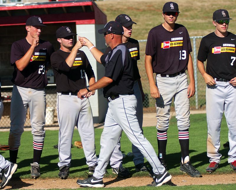 Photo Credit: DAN BROOD - GOOD JOB -- Sherwood head coach Jon Strohmaier congratulates the Bowmen players following their 5-4 win over Lake Oswego in the OIBA tournament championship game played Saturday at Oregon City High School.