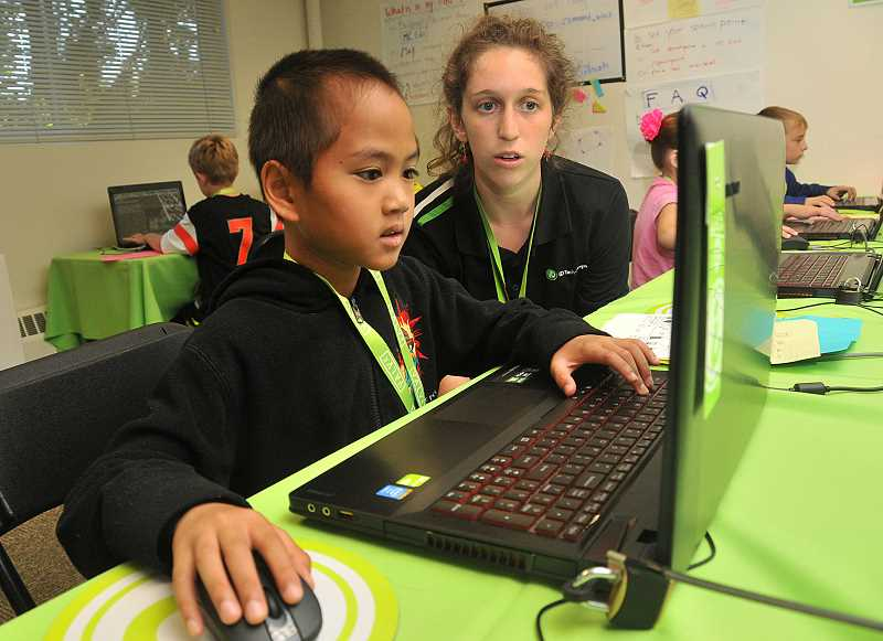 Photo Credit: REVIEW PHOTO: VERN UYETAKE - Lee Mair, 8, of Lake Oswego receives some help from camp counselor Simone Wood. Lees using MCEdit for the first time to program a Minecraft video game.