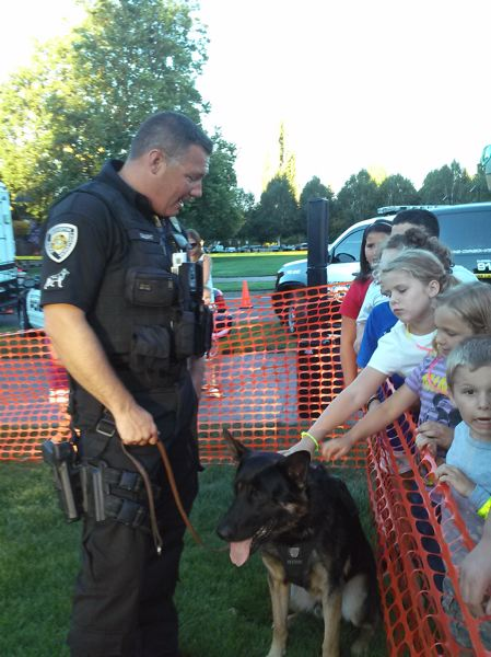 Photo Credit: TIMES PHOTO: SHANNON O. WELLS - Beaverton police officer Brian Gaunt introduces children to Ike, the newest K9 in the Beaverton Police Department, at the National Night Out event on Tuesday evening.