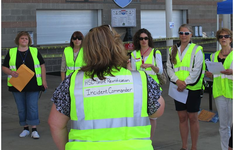 Photo Credit: HILLSBORO TRIBUNE PHOTOS: KATHY FULLER - Members of the parent reunification team listen to instructions prior to the beginning of a small-scale drill on July 30.