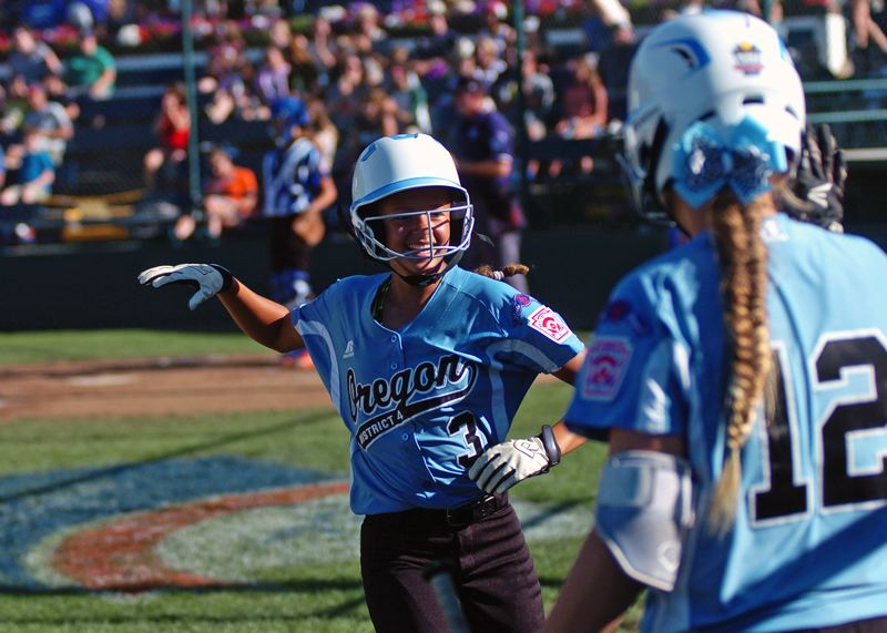 Photo Credit: DAN BROOD - FUN TIMES -- Tigard/TC's Tia Cordts (left) is all smiles as she runs up to teammate Emily Harms after scoring in the fifth inning of the team's 7-5 win over Prague Saturday at the Little League Softball World Series.