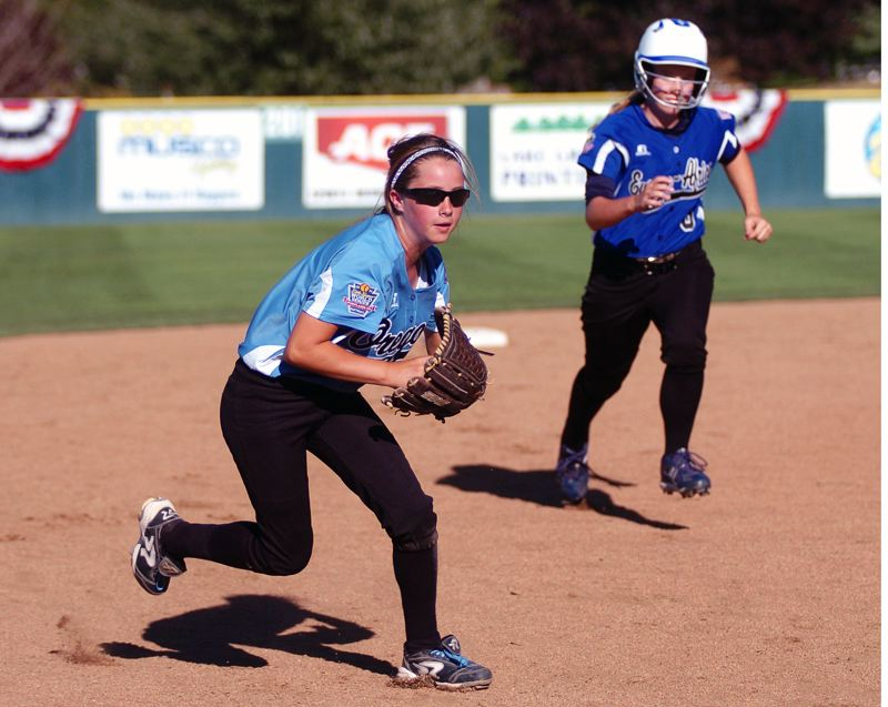 Photo Credit: DAN BROOD - IN THE CLUTCH -- Tigard/Tualatin City shortstop Bella Valdes (left) sprints to third base ahead of Prague's Michaela Otahalova to get a key out in the sixth inning of Saturday's Little League Softball World Series game.