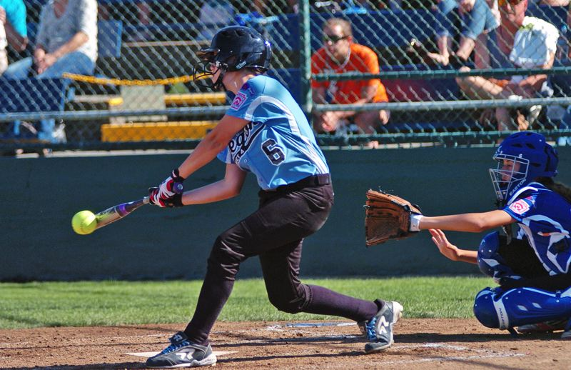 Photo Credit: DAN BROOD - MAKING CONTACT -- Tigard/TC's Logan Mentzer gets her bat on the ball during the team's 7-5 win over Prague Saturday at the Little League Softball World Series.