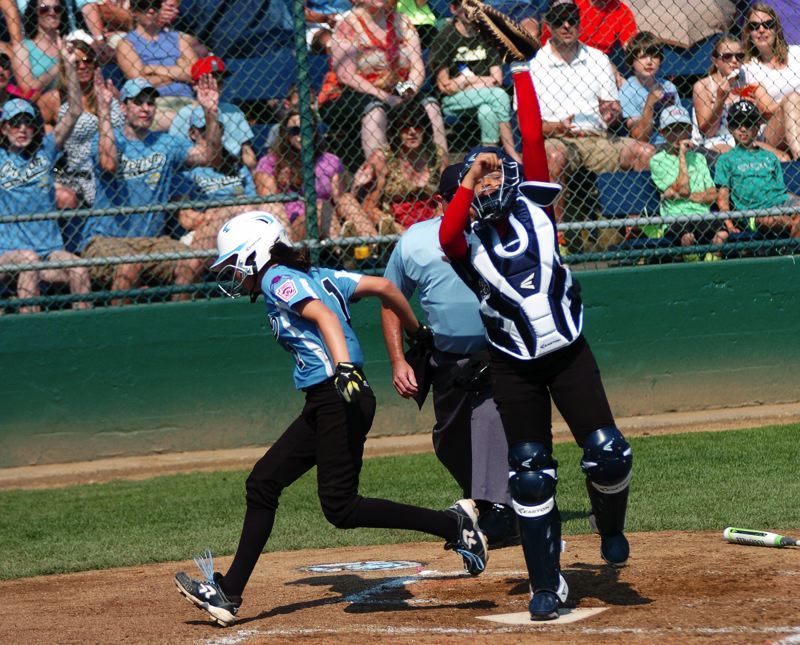 Photo Credit: DAN BROOD - EQUALIZER -- Tigard/TC's Alexis Klum (left) crosses home plate to tie Sunday's game at 1-1.
