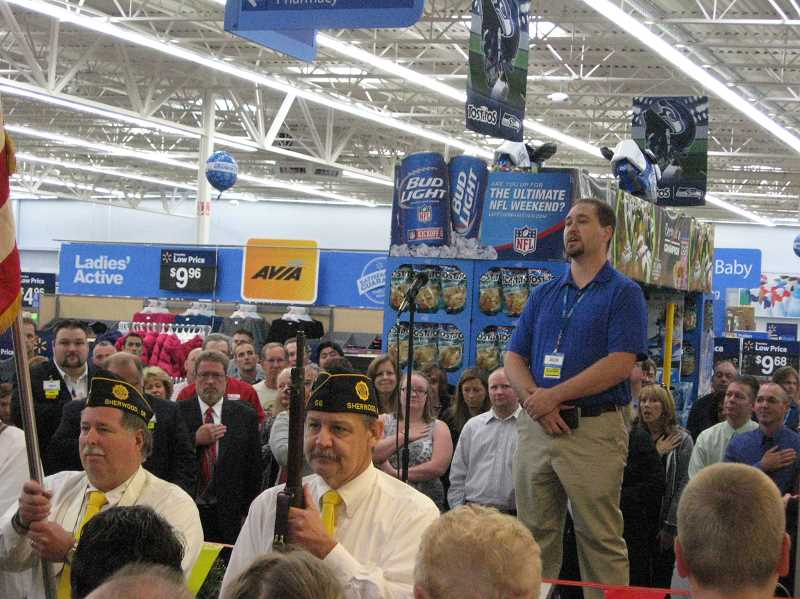 Photo Credit: GAZETTE PHOTO: RAY PITZ - Joseph Battrick, a Sherwood Walmart store employee (flanked by a color guard from the Sherwood American Legion) sings the Star-Spangled Banner during opening ceremonies at the Sherwood Walmart store Wednesday. Grocery