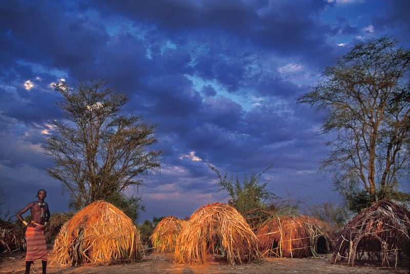 Photo Credit: PHOTO COURTESY OF JANIS MIGLAVS - Mursi huts keep their occupants safe from the oncoming storm in Ethiopia, Africa.