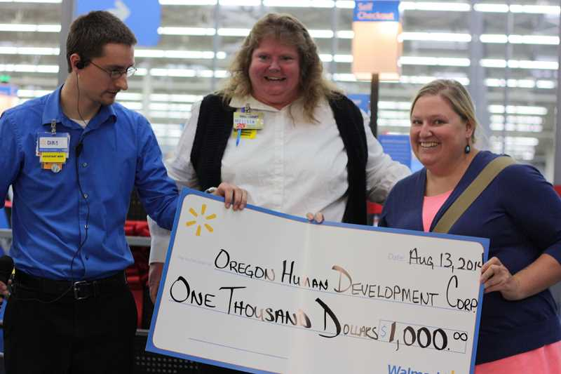 Mia Barlett, who runs the Oregon Human Development Corp's YouthSource program in Metzger, accepts a a $1,000 grant from Walmart, which opened its doors on Aug. 13. The store awarded thousands of dollars to local charities and programs across the Portland area.