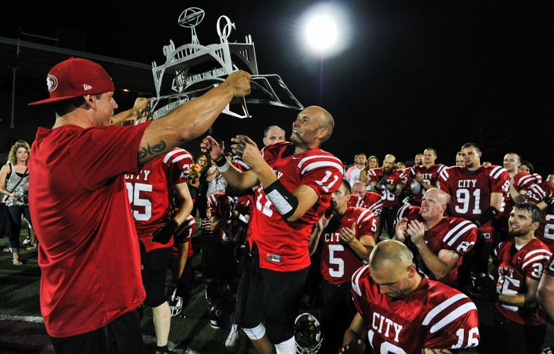 Photo Credit: JOHN LARIVIERE - Justin Fisher accepts the Battle for the Bridge trophy for Oregon Citys alumni team following the Pioneers 24-9 win over cross-river rival West Linn in the 2014 Battle for the Bridge alumni football game.