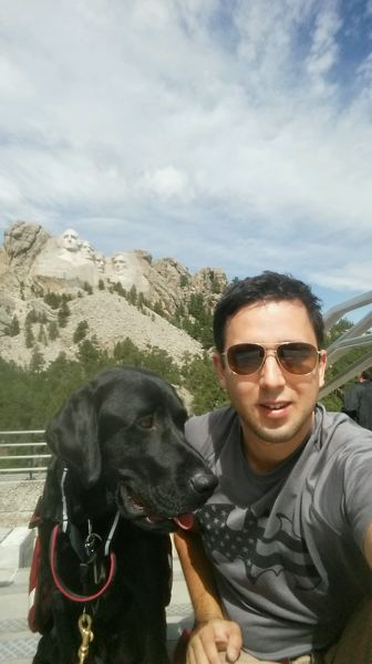 Photo Credit: COURTESY OF PATRICK DEMONT - Patrick Demont and his new companion Tolkien stop for a photo together at Mount Rushmore. Demont said he has already noticed a difference in his demeanor since he got Tolkien.