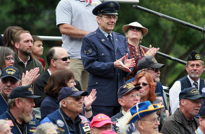 FILE - Veterans and other attendees at a past Memorial Day program in Beaverton applaud.