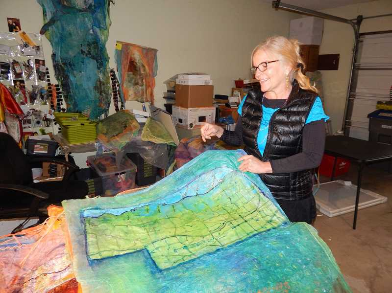 REGAL COURIER PHOTO: BARBARA SHERMAN - In her workshop, aka the Strom/Moyers garage, Sal Strom sifts through a pile of the maps of each state they will drive through that she has decorated with colorful cheesecloth.