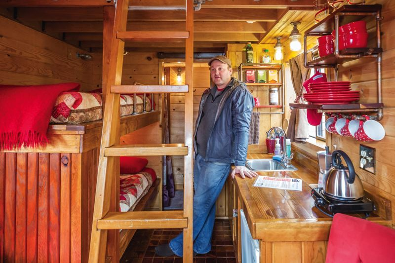 TRIBUNE PHOTOS: JONATHAN HOUSE - Kol Peterson shows features inside one of the tiny houses at Carvan, the Tiny House Hotel. Occupancy at the hotel topped 90 percent last year.