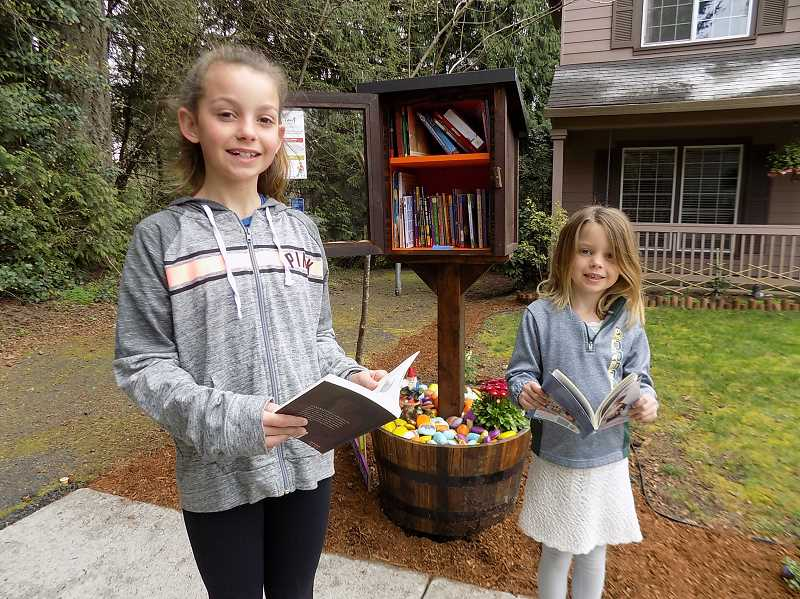 GAZETTE PHOTO: RAY PITZ  - Kaia, a fifth-grader at Archer Glen Elementary School, left, and Isla, a first-grader at Archer Glen, both got to select the first books to be installed in the new Little Free Library their mother Rebecca King helped to set up on Redfern Drive.