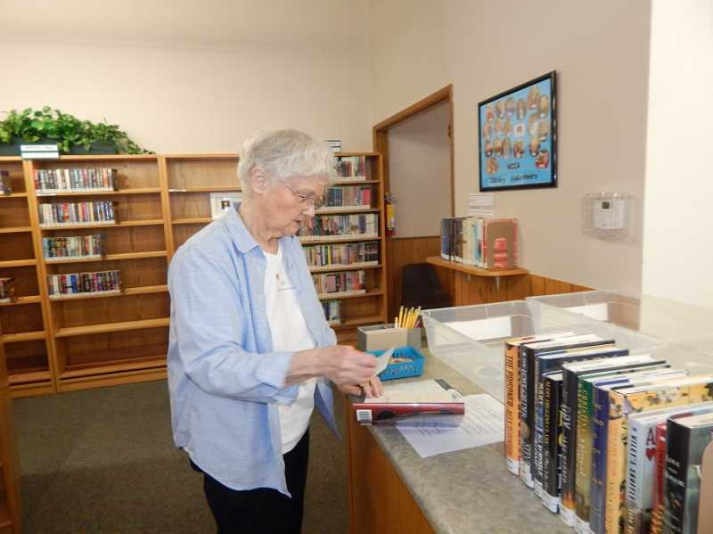 REGAL COURIER PHOTO: BARBARA SHERMAN - KCCA library volunteer Carol Heisler looks at a card in a book to make sure it is ready to be checked out; on the wall on the right is a collage of photos of all the library volunteers.