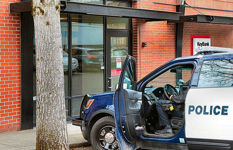 DAVID F. ASHTON - This branch of KeyBank is closed for the rest of the day; an officer writes up a report on the incident inside his patrol car.