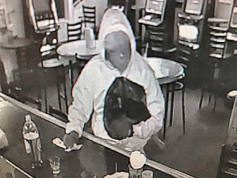 SURVEILLANCE PHOTO - Heres an image of the armed robber, face obscured by a mask, sitting at the bar.