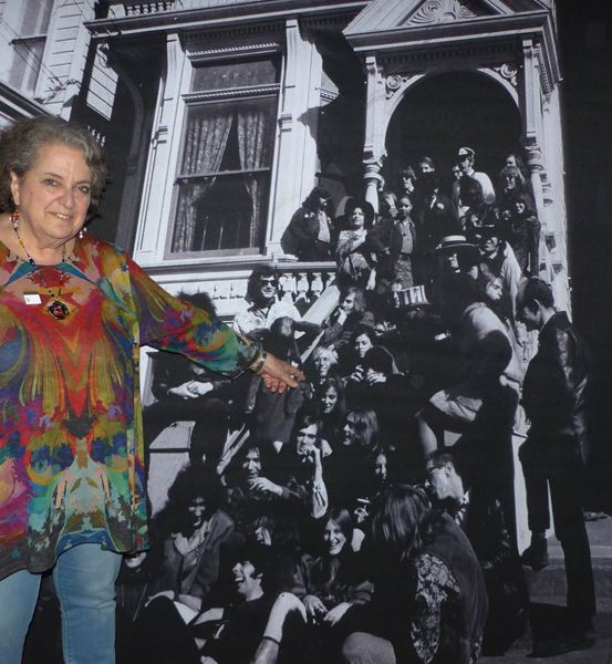 ORIGINAL PHOTO AT 710 ASHBURY BY GENE ANTHONY; PHOTO OF ROSIE MCGEE BY SUSANA MILLMAN - Rosie McGee points to her younger self at San Franciscos de Young Museum's 'The Summer of Love Experience' exhibition, which featured a photo taken by Gene Anthony in 1967 of five San Francisco bands and their families, gathered on the steps of the Grateful Dead's residence.