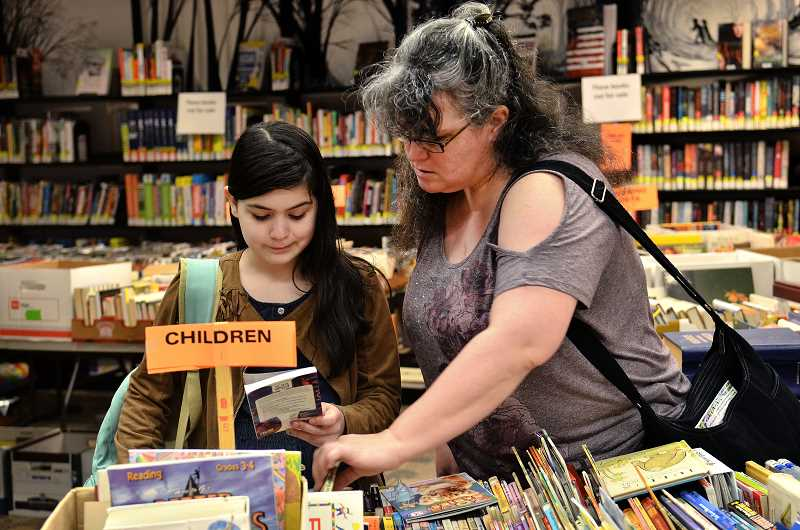 TIDINGS PHOTOS: VERN UYETAKE - Kelly and Morgan, 10, Griffin of West Linn look for some bargains in the childrens section at last weeks book sale at the West Linn Public Library.