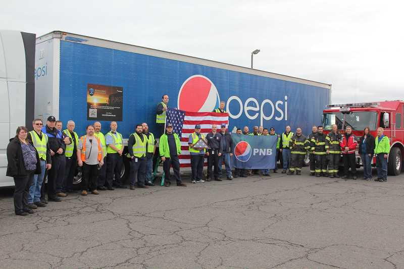 LINDSAY KEEFER - The Rolling Remembrance truck stopped in Mount Angel on April 25 on the second day of its relay around the U.S. Pepsi Northwest Beverage employees, as well as local fire and city personnel, joined for the photo op. The truck was escorted out of town by Mount Angel fire and police.
