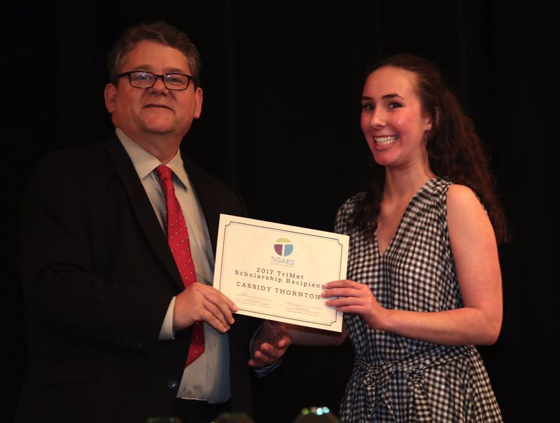 TIMES PHOTO: JAIME VALDEZ - Cassidy Thornton, right, accepts an honor as the recipient of the 2017 TriMet Scholarship from Tom Markgraf, TriMet's public affairs director, at the Shining Stars Awards Celebration.