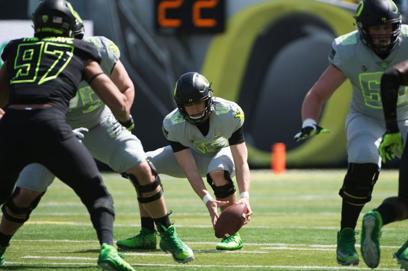 TRIBUNE PHOTO: CHRISTOPHER OERTELL - Oregon Ducks quarterback Justin Hebert fields a low snap during the Saturday spring game at Autzen Stadium.