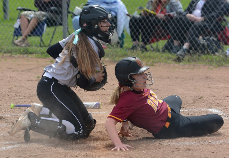 OUTLOOK PHOTO: DAVID BALL - Reynolds catcher Raven Laine and Central Catholics Abby LeDoux look to the umpire for a ruling on a play at the plate in the first inning. The runner was called out.