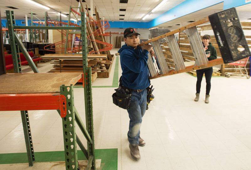 OUTLOOK PHOTO: JOSH KULLA - Electrician Thanh Nguyen takes his ladder to another part of the brand new ReStore, a Habitat for Humanity-run re-sale shop that soon will open to the public and offer building materials, furniture and other home improvement products.
