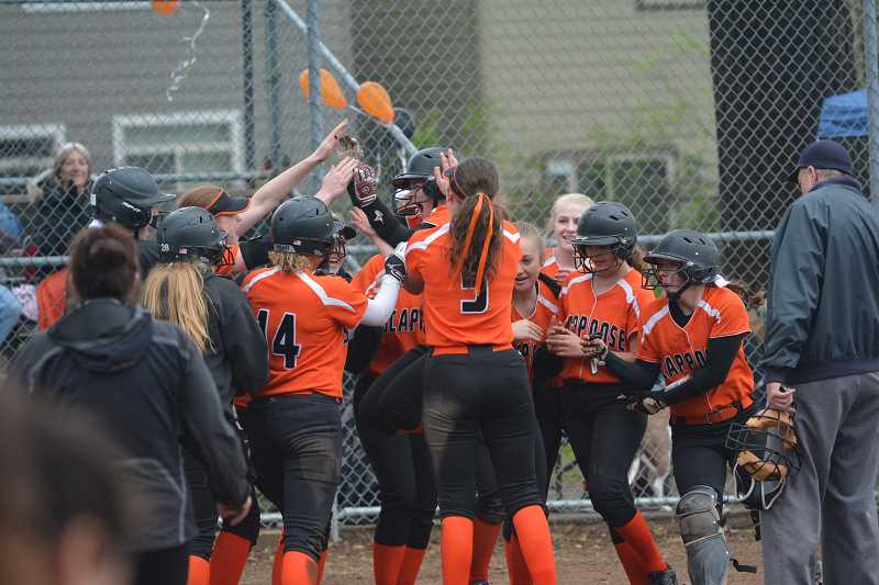 SPOTLIGHT PHOTO: JAKE MCNEAL - Indians senior Nicole Lukinbeal and the No. 4 Indians celebrate her third-inning grand slam in a 14-2 Senior Night defeat of Seaside on Monday in Scappoose.