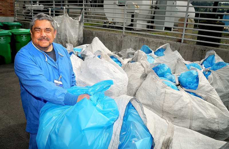 GARY ALLEN - Glenn Monzon, manager of environmental services at Providence Newberg Medical Center, stands with bags of recyclables being sent to Providence's central recycling facility. The Newberg hospital recently gained recognition for its environmental sustainability efforts when it won the Partner for Change Award from Practice Greenhealth, a nonprofit organization promoting sustainable practices in the health care sector.