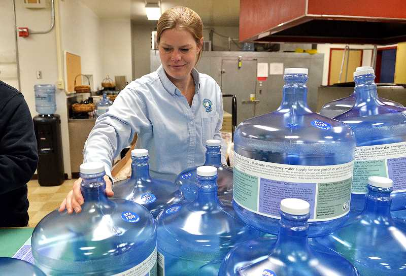 REVIEW PHOTO: VERN UYETAKE - Kari Duncan, who manages Lake Oswego's water treatment plant, gets three-gallon water storage jugs ready for distribution at the Emergency Preparedness Fair.