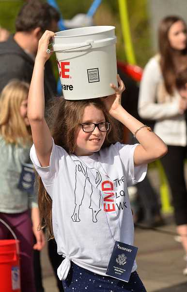 REVIEW PHOTO: VERN UYETAKE - Julia Barber practices carrying her bucket on her head during Saturday's Walk4Water, a two-mile round trip from Foothills Park to Millennium Plaza and back.