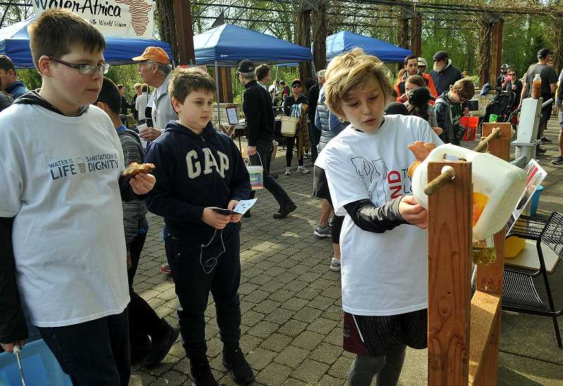 REVIEW PHOTO: VERN UYETAKE - Henry Pinetner demonstrates a tip-tap water dispenser used by villagers in Africa at one of 10 informational booths staffed by students at the Walk4Water on Saturday.