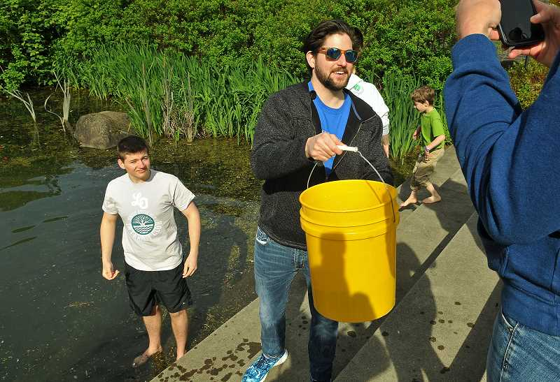 REVIEW PHOTO: VERN UYETAKE - Mike Olen (left) and Stuart Allen fill buckets on Saturday for participants in the Walk4Water, which wound from Foothills Park to Millennium Plaza and back.