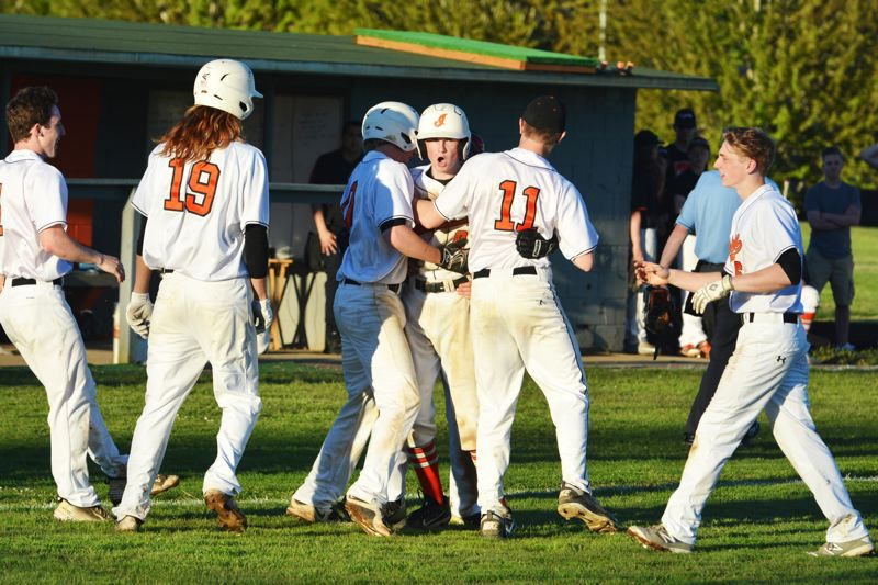SPOTLIGHT PHOTO: JAKE MCNEAL - Indians junior JC Gross (8) celebrates his walk-off hit to center field and a 9-8, eight-inning win over No. 3 Astoria with, from left, junior Jerad Toman, senior Quinn Searle (19), junior Nicky Gill and seniors Zach Knight and Ben Teeter on Wednesday in Scappoose.