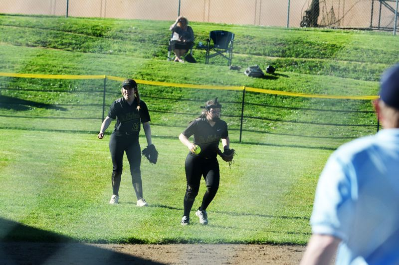 SPOTLIGHT PHOTO: JAKE MCNEAL - Lions junior Kortney Smith, left, and sophomore Taylor Dow, right, relay a flyout.