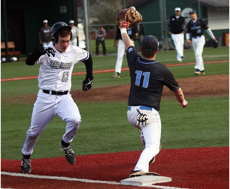 DAN BROOD - Tigard High School senior Hunter Hughes (left) races to first base as Lakeridge's Tommy Andrew reaches for the ball during last week's game.