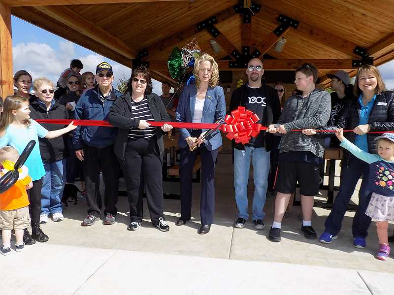 GAZETTE PHOTO: RAY PITZ - Sherwood Mayor Krisanna Clark, center, cuts a ribbon, accompanied by members of the Sherwood City Council, during a grand reopening of Woodhaven Park on May 6.