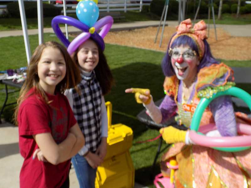 GAZETTE PHOTO: RAY PITZ - Cha Cha the Clown ties balloons for Janessa Morris, right, and Grace Steffens during grand reopening ceremonies at Woodhaven Park on May 6.