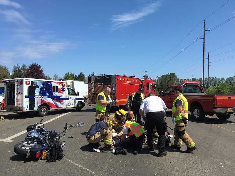 COURTESY PHOTO: FOREST GROVE FIRE & RESCUE - Emergency responders work on a critically injured motorcycle rider at the intersection of Highway 47 and Fernhill Road.