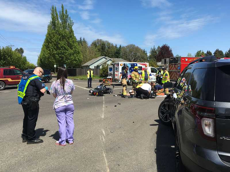 COURTESY PHOTO: FOREST GROVE FIRE & RESCUE - A Forest Grove police officer talks to a witness to the crash at Highway 47 and Fernhill Road while emergency responders work to save a seriously injured motorcycle rider.