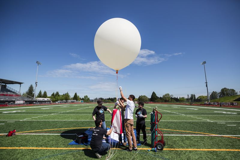 TIMES PHOTO: JONATHAN HOUSE - Oregon Institute of Technology students, guided by assistant professor Leif Taylor, practice releasing a smaller version of their eclipse-tracking balloon during a dry run at Tualatin High School on Monday.