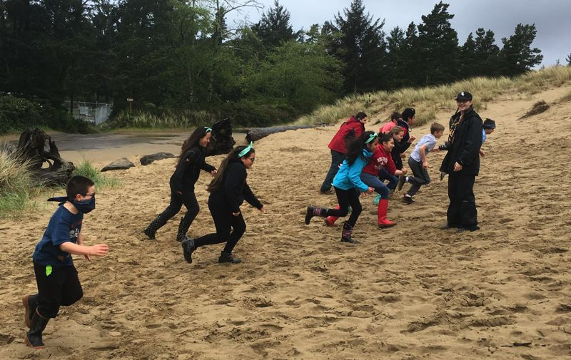 Emily McClaflin, a senior at Gladstone High School who obtained a coveted spot as a counselor at Outdoor School, watches sixth-graders run to study dune ecosystems at Rockaway Beach on the Oregon Coast.