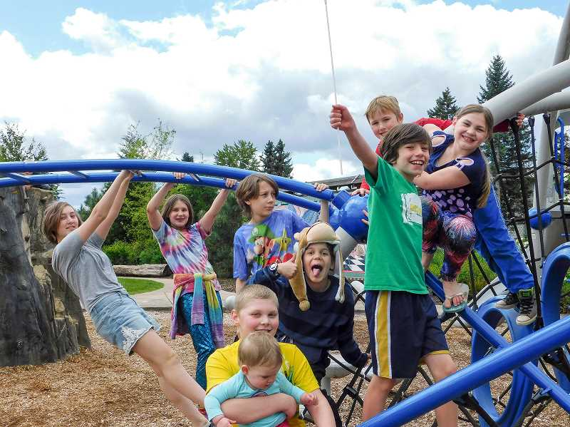 ESTACADA NEWS PHOTO: EMILY LINDSTRAND - Young residents enthusiastically gather for a photo on the playground at Wade Creek Park during the anniversary celebration last weekend. 'We're doing this for Estacada,' they chanted before running to the playground.